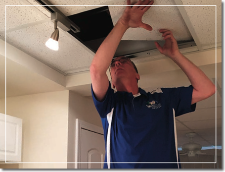 Home inspector Rob Gisch inspecting a drop ceiling