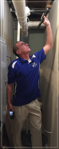 Man wearing glasses and a cobalt blue shirt and tan pants peering at ceiling with flashlight.