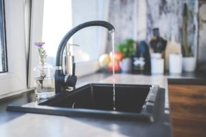 Black kitchen sink with water running from faucet.
