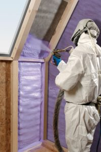 Man in white protective suit spraying purple spray insulation between the rafters of a new home.