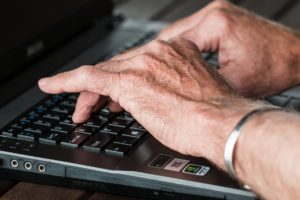 Hands typing on a black laptop keyboard