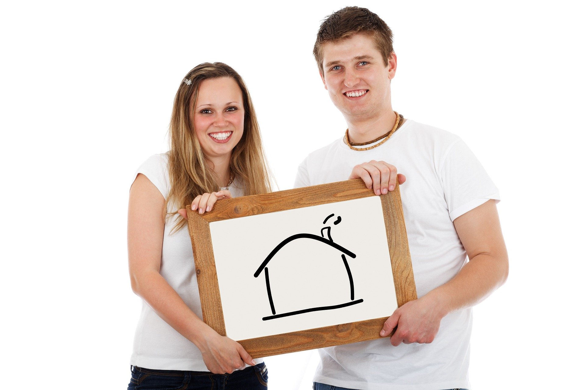 Young man and woman in white holding a drawing of a home