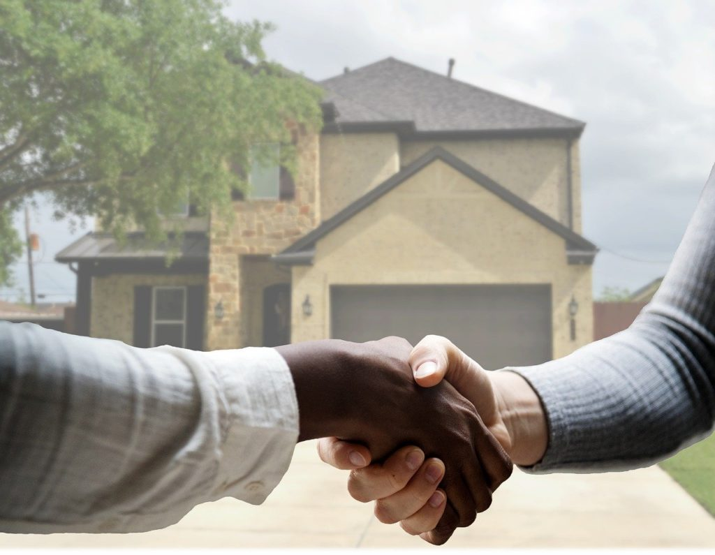 shaking hands in front of new house