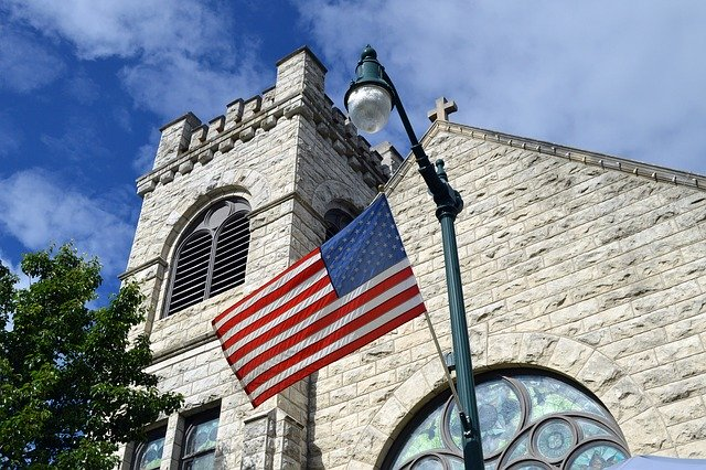 American flag in front of stone church
